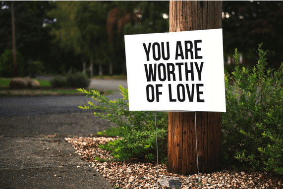 Self Love Is The Best Love, image of a white sign with the phrase you are worthy of love, sitting in front of a tree on a path