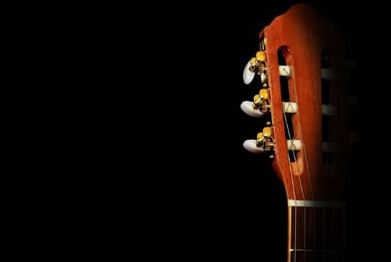 Don't settle, dark background with the top of a guitar, shadow on the right side of the guitar.