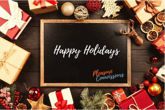Happy holidays, chalboard with the words happy holidays in white and the Pleasure Connoisseurs logo in orange and blue, the board is surrounded by gifts wrapped in red and gold.