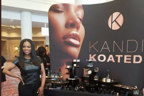 Kandi Coated Makeup: Bedroom Kandi, image of Kandi Burruss in front of a banner and display for her new cosmetics.