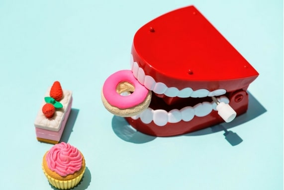 Summer 100. Oral Play Is Not A Game, image of a wind up toy teeth and toy pastries.