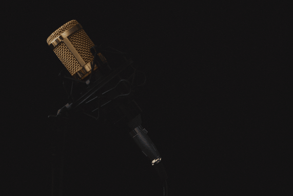 Public service announcement, image of a a gold microphone, black background