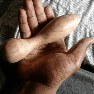 Lumberjill, adult wooden sex toy, image of a hand holding an unfinished wooden dildo.