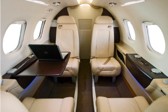 Meet Your Captain, Pleasure Connoisseurs cabin, image of the inside of a private jet, cream leather seats, dark wood glossy, finishing.