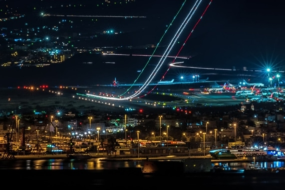 Additional Featured Attractions, airport at night, airplane taking off with a trail of lights